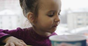 Stående av lite flickan i ett kafé nära fönstret arkivfilmer