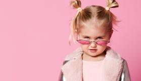 Stående av lite flickan i stilfulla kläder som poserar på rosa bakgrund och spelar upp arkivfoto