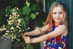 Stående av lite flickan med tusenskönor Älskvärt behandla som ett barn med blommor Arkivfoton
