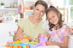 Stående av lite flickan och hennes spela för moder arkivbild