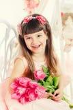 Stående av lite flickan, rosa tulpan i händer Royaltyfria Foton