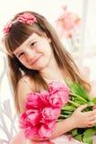 Stående av lite flickan, rosa tulpan i händer Arkivfoton