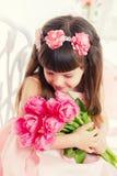 Stående av lite flickan, rosa tulpan i händer Royaltyfri Bild