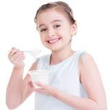 Stående av lite flickan som äter yoghurt. Arkivfoton