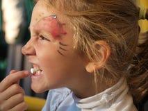Stående av lite flickan som rymmer en marshmallow i hennes tänder royaltyfri bild