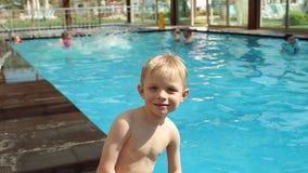 Stående av lite pojken i barnens pöl på hotellet på semester lager videofilmer