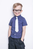 Stående av lite pojken i roligt exponeringsglas och band skola förträning Mode Studiostående som isoleras över vit bakgrund arkivbilder