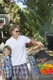 Stående av lite pojken med fadern som grillar grönsaken på grillfestgaller i gräsmatta Royaltyfri Bild