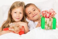 Stående av lite pojken och flickan med gåvor i händer Royaltyfri Bild