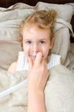 Stående av liten flicka som ligger i säng med inhalatoren Fotografering för Bildbyråer
