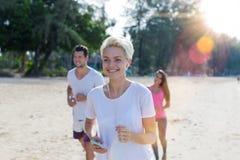 Stående av lycklig le kvinnaspring på stranden med gruppen av unga sportlöpare som tillsammans joggar kondition royaltyfria bilder