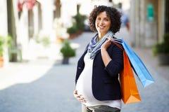 Stående av lycklig och le gravid kvinnashopping arkivfoton