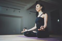 Stående av lycklig praktiserande yoga för ung kvinna inomhus Härlig position för flickaövningslotusblomma i grupp Lugn och koppla arkivfoton