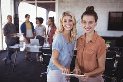 Stående av lyckliga affärskvinnor som rymmer den digitala minnestavlan med det idérika laget royaltyfria bilder