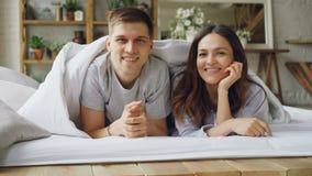 Stående av lyckliga blandad-lopp par som från under dyker upp filten, ler och ser kameran Lyckligt gift liv arkivfilmer