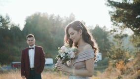Stående av lyckliga brölloppar på naturen Bruden som sniffar blommor lager videofilmer