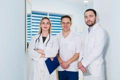 Stående av lyckliga cowerkers med skrivplattan, medan stå på sjukhuset royaltyfria bilder