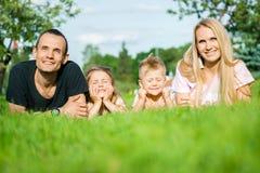 Stående av lyckliga föräldrar med ungar som ligger på parkera royaltyfri fotografi