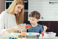 Stående av lyckliga för målningpåsk för ung kvinna ägg med hennes förtjusande lilla son arkivfoto