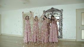 Stående av lyckliga flickor i aftonklänning som upp inomhus kastar guld- omslag arkivfilmer