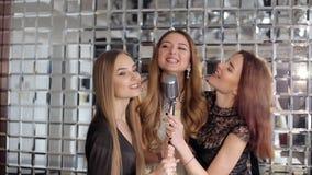 Stående av lyckliga flickor som sjunger i mikrofon i karaokestången lager videofilmer