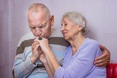 Stående av lyckliga höga par, man som kysser handen arkivfoto