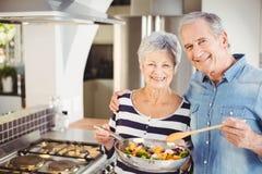 Stående av lyckliga höga par med matlagningpannan arkivbild
