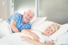 Stående av lyckliga höga par som kopplar av på säng Royaltyfri Fotografi
