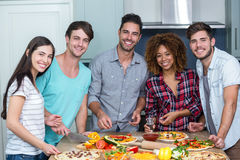Stående av lyckliga mång--person som tillhör en etnisk minoritet vänner som hemma förbereder pizza royaltyfri bild