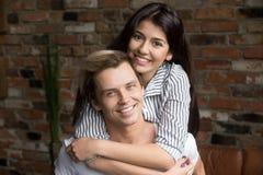 Stående av lyckliga millennial par som kramar att posera för familjal royaltyfri foto