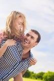 Stående av lyckliga och gladlynta unga Caucasian par Piggybacki Royaltyfri Bild