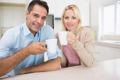 Stående av lyckliga par med kaffekoppar i kök Arkivbilder