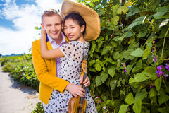 Stående av lyckliga par som omfamnar vid växter arkivbild