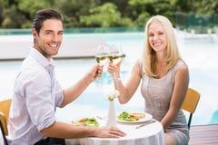 Stående av lyckliga par som rostar exponeringsglas för vitt vin Royaltyfria Foton