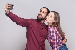 Stående av lyckliga par som står, ser och kysser på kameran av den mobila smarta telefonen för att göra selfie eller den videopd  royaltyfria bilder