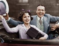 Stående av lyckliga par som vinkar i bil (alla visade personer inte är längre uppehälle, och inget gods finns Leverantörgarantier royaltyfri bild