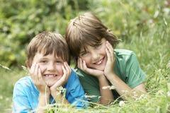 Stående av lyckliga pojkar som ligger i gräs royaltyfria bilder