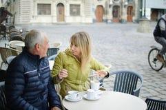 St?ende av lyckliga romantiska par med ?lderskillnaden som utomhus dricker kaffe i kaf? med terrassen i den forntida staden arkivfoto