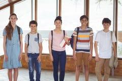 Stående av lyckliga studenter som står i korridor royaltyfri foto