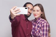 Stående av lyckliga tillfredsställda par som står, ser och ler på smartphonekameran för att göra selfie eller den videopd appelle fotografering för bildbyråer