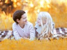 Stående av lyckliga två barn, pojken och flickan som tillsammans ligger Arkivbild