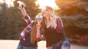 Stående av lyckliga två le flickor som gör selfiefotoet på smartphonen stads- bakgrund Aftonsolnedgången över stock video