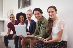 Stående av lyckliga unga affärskollegor som tillsammans arbetar vid väggen på kontoret royaltyfri fotografi