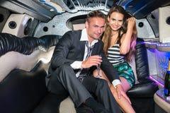 Stående av lyckliga unga glamorösa par med champagneflöjten in arkivbild
