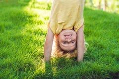 Stående av lyckliga ungar som spelar uppochnervänd det fria i sommar p Royaltyfria Foton