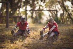Stående av lyckliga ungar som utför sträcka övning under hinderkurs arkivbilder