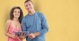 Stående av lyckligt affärsfolk med den digitala minnestavlan mot gul bakgrund Fotografering för Bildbyråer