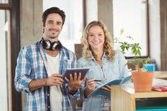 Stående av lyckligt affärsfolk som rymmer den digitala minnestavlan i idérikt kontor Arkivfoton
