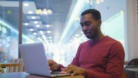 Stående av lyckligt afrikanskt affärsmansammanträde i ett kafé och arbete på bärbara datorn royaltyfri foto