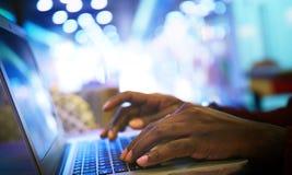 Stående av lyckligt afrikanskt affärsmansammanträde i ett kafé och arbete på bärbara datorn arkivbild
